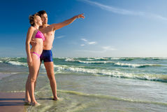 Happy couple on a beach-3. Happy couple on a beach pointing to the horizon Royalty Free Stock Photography