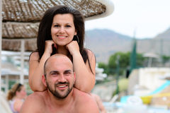 Happy  couple    on the beach. Beautiful smiling tanned bearded muscular men and smiling brunette  hugging on  the beach in luxury hotel Stock Photo