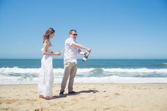 Happy couple on the beach with champagne Royalty Free Stock Images