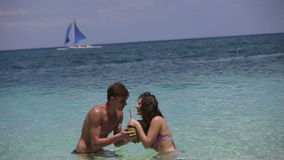 Happy couple on the beach with coconut stock footage