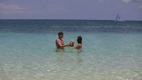 Happy couple on the beach with coconut stock video footage