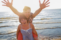 Happy couple on the beach. Girl holds her boyfriend on back. Stock Image