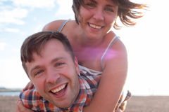 Happy couple on the beach. Girl holds her boyfriend on back. Royalty Free Stock Images