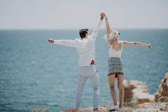 Happy couple on beach hold raised up arms, stretching hands on ocean view. Beautiful young happy man and woman enjoy summer. conce royalty free stock photography