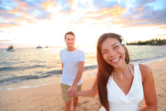Happy couple on beach holding hands at sunset Stock Images