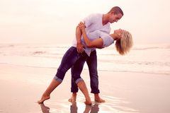 Happy couple on a beach. Loving couple enjoying the time spent together on the beach, standing bare foot in the water Royalty Free Stock Images