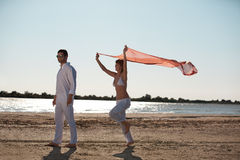 Happy couple on the beach scarf wind Royalty Free Stock Photos