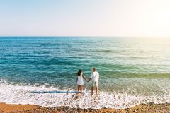 Happy couple on the beach with their backs to the camera. Honeymoon trip. The couple are traveling. Man and woman on the beach. Happy couple on the beach with royalty free stock image
