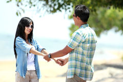 Happy couple by the beach together in holding hands Royalty Free Stock Photos