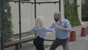 Happy couple of bearded strong business man and young cute woman street dancing latino salsa in bus station -. Happy couple of bearded strong business man and stock video footage