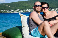 Happy  couple. Beautiful smiling tanned bearded muscular men and smiling brunette  hugging on  the pier in luxury hotel Royalty Free Stock Photos