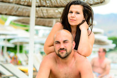 Happy  couple. Beautiful smiling tanned bearded muscular men and smiling brunette  hugging on  the pool in luxury hotel Stock Photos