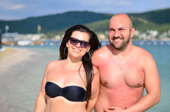 Happy  couple. Beautiful smiling tanned bearded muscular men and smiling brunette  hugging on  the pool in luxury hotel Royalty Free Stock Photo