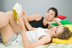 Happy couple in bed with book Royalty Free Stock Photo