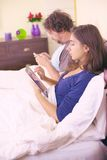 Happy couple in bed having fun with cell phone and tablet retro style Royalty Free Stock Image