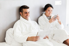 Happy couple in bed at home or hotel room Stock Images