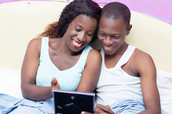 Happy couple in the bed looking at a photo. royalty free stock photo