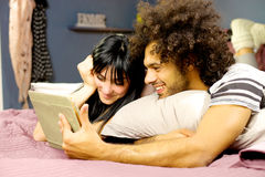 Happy couple in bed reading tablet having fun and relax Stock Photography