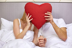 Happy couple in bed with red heart shape pillow Royalty Free Stock Photo