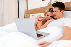 Happy couple in bed using laptop. Happy couple in bed using notebook and smiling Stock Photography