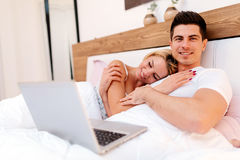 Happy couple in bed using laptop. Happy couple in bed using notebook and smiling Royalty Free Stock Photos