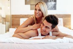 Happy couple in bedroom. Enjoying sensual foreplay royalty free stock images
