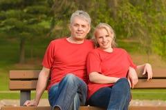Happy couple on the bench Stock Photos