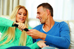 Happy couple bickering to change tv channel Stock Photos