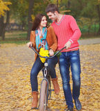 Happy couple with bicycle in autumn park Stock Images