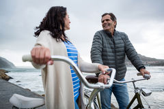 Happy couple on bicycle interacting with each other Royalty Free Stock Images