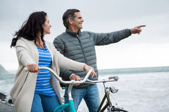 Happy couple on bicycle pointing at distance on beach Royalty Free Stock Photo