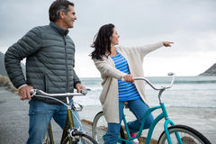 Happy couple on bicycle pointing at distance on beach Royalty Free Stock Photography
