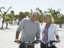 Happy Couple With Bicycles On Tropical Beach Royalty Free Stock Photography