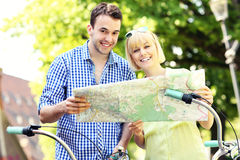 Happy couple on bikes with a map Royalty Free Stock Photos