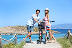 Happy couple with bikes standing by the shore royalty free stock photography