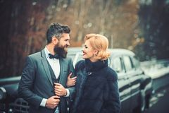 Happy couple at black vintage retro car. Friends going on road trip travel on winter day royalty free stock photo