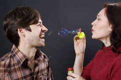 Happy couple blowing bubbles Stock Image