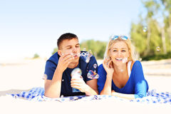 Happy couple blowing bubbles at the beach Stock Photography