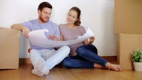 Happy couple with blueprint at new home stock video footage