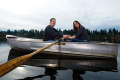 Happy couple on a boat. A happy young couple rowing a small boat on a quiet lake Stock Photos