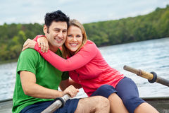 Happy couple in a boat. A happy early 30s caucasian couple in a rowboat on a lake Royalty Free Stock Photos