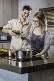 Happy couple bonding together while cooking a meal in the kitchen drinking wine Stock Photography