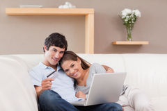 Happy couple booking vacations online Stock Images