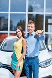 Happy couple bought a new car and shows the keys to it. Stock Photography