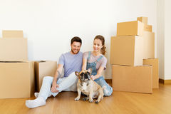 Happy couple with boxes and dog moving to new home. Mortgage, people and real estate concept - happy couple with boxes and french bulldog dog moving to new home Stock Images