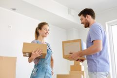 Happy couple with boxes moving to new home Royalty Free Stock Images