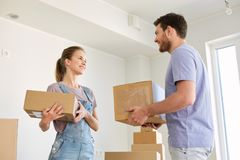 Happy couple with boxes moving to new home Royalty Free Stock Photo