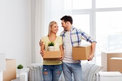 Happy couple with boxes moving to new home. Mortgage, people and real estate concept - happy couple with boxes moving to new home royalty free stock images
