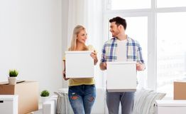 Happy couple with boxes moving to new home. Mortgage, people and real estate concept - happy couple with boxes moving to new home royalty free stock photography