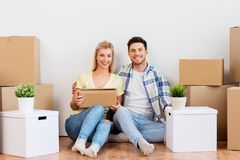Happy couple with boxes moving to new home royalty free stock photos
